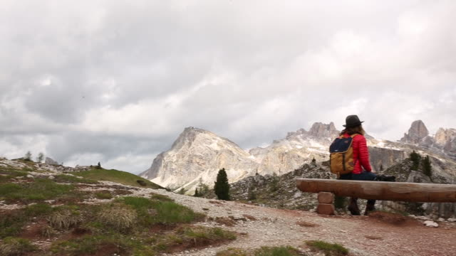 a young woman day hiking in the dolomite mountains of italy. - one mid adult man only stock videos & royalty-free footage