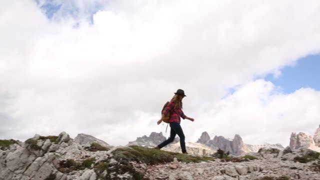 vídeos de stock e filmes b-roll de a young woman day hiking in the dolomite mountains of italy. - só um homem de idade mediana