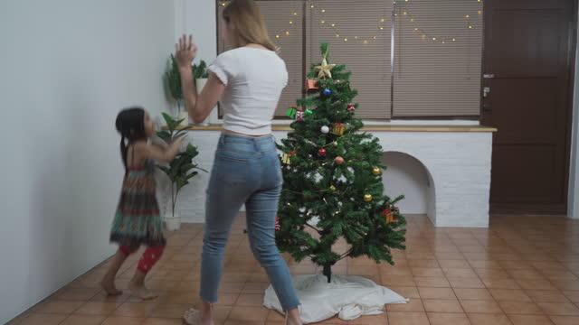 stockvideo's en b-roll-footage met jonge vrouw die kerstboom met weinig leuk meisje verfraait - cadeau