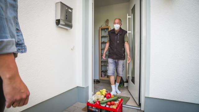 young woman delivering groceries to front door of a senior man during coronavirus quarantine - assistance stock videos & royalty-free footage