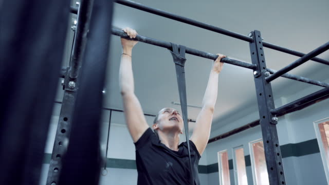 young woman determined to do chin-ups on fixed bar. - struggle stock videos & royalty-free footage
