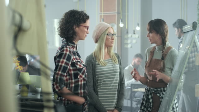 Young woman discussing with colleagues in office