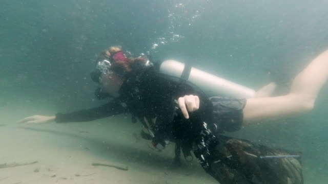 young woman dive against debris underwater garbage cleanup - aqualung diving equipment stock videos & royalty-free footage