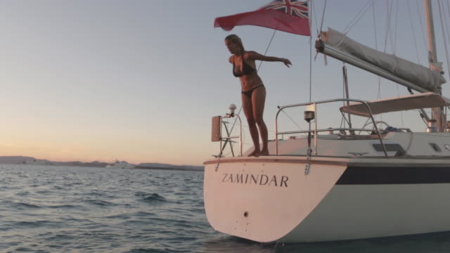 ms a young woman dives into the water from a sailing boat at sunset / ibiza, spain - 小型船舶点の映像素材/bロール