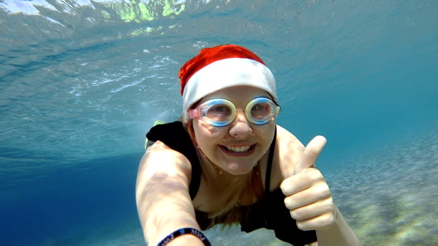 Young woman diving in Santa Claus hat