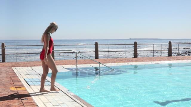 vidéos et rushes de young woman diving into swimming pool - plonger dans l'eau