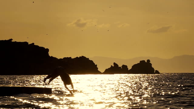 young woman diving into water at sunset - diving into water stock videos & royalty-free footage