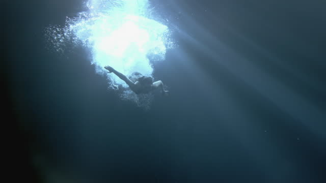 WS SLO MO Young woman diving underwater / London, United Kingdom