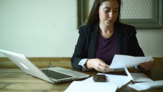 Young woman do office paperwork, opening and reading letters.