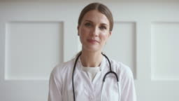 Young woman doctor talk by video chat consult patient online