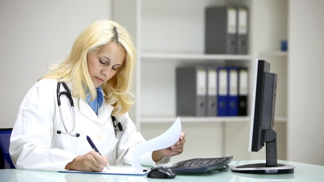 Young woman doctor writing in doctors's office