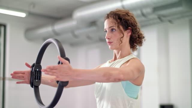 young woman does pilates exercises using a pilates ring - abbigliamento sportivo video stock e b–roll