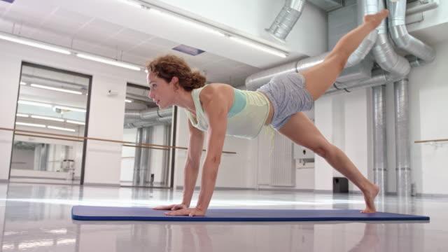 vídeos de stock, filmes e b-roll de young woman (fitness trainer) does pilates exercises - cabelo de comprimento médio