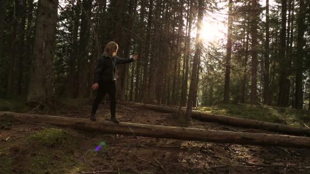 Junge Frau macht Yoga auf gefallene Wald log