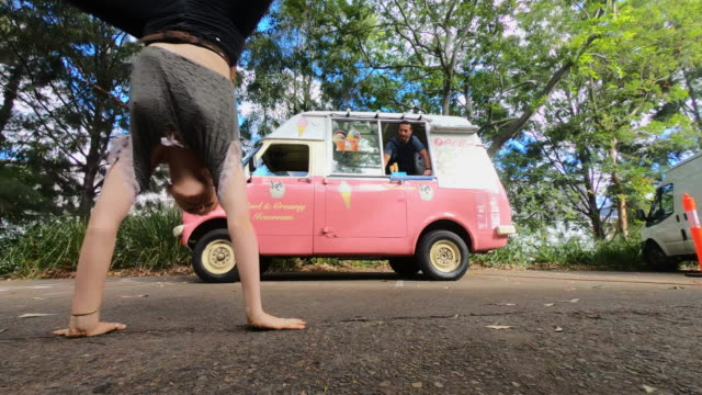 young woman doing a cartwheel in front of an icecream truck - cartwheel stock videos & royalty-free footage