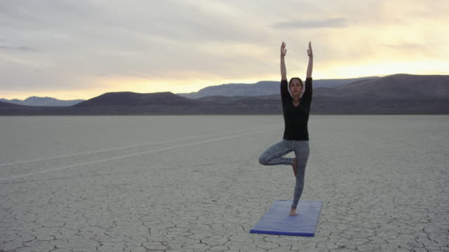 4k uhd: young woman doing a tree yoga pose adesert sunset - balance stock videos and b-roll footage