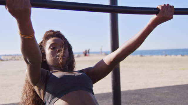 young woman doing chin-ups on jungle gym - chin ups stock videos and b-roll footage