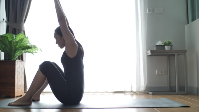 young woman doing exercise in living room at home - exercise room stock videos & royalty-free footage