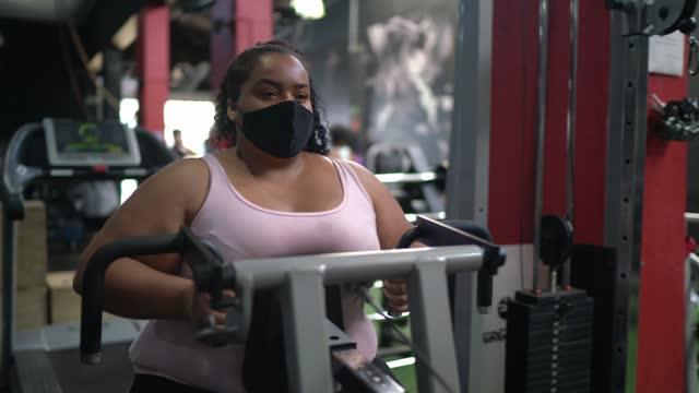 vídeos de stock, filmes e b-roll de jovem fazendo exercício na academia usando máscara facial - on the move