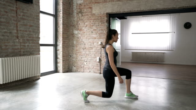 Young Woman Doing Forward Lunges At Home