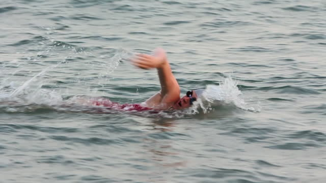 vídeos de stock, filmes e b-roll de ws slomo young woman doing freestyle swimming in sea/singapore - touca de natação