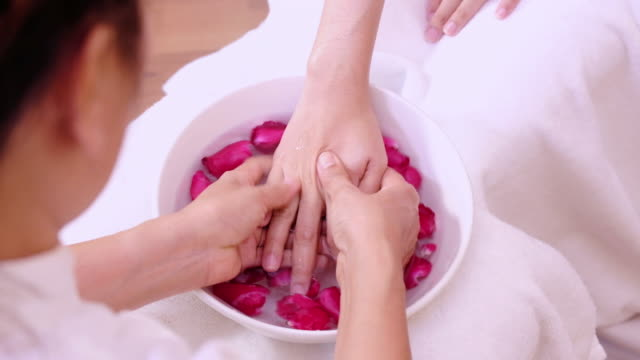 Young woman doing hand spa massage.