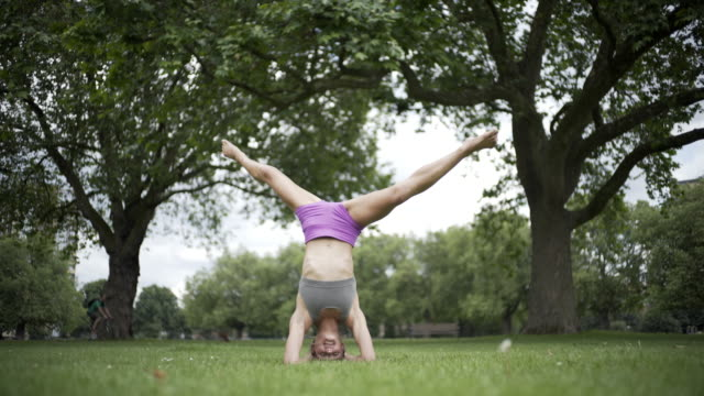 A young woman doing head stands and yoga in the park