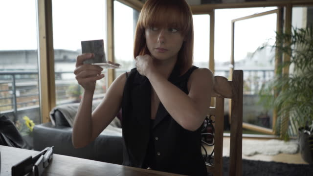 vidéos et rushes de a young woman doing her make-up while texting  on a smart phone - hair straighteners