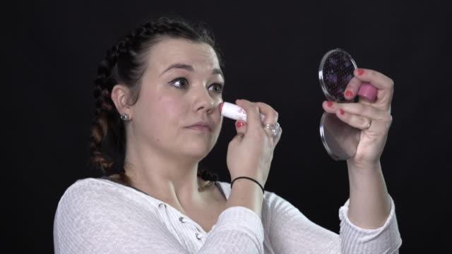 vídeos de stock, filmes e b-roll de a young woman doing her own make-up - blush