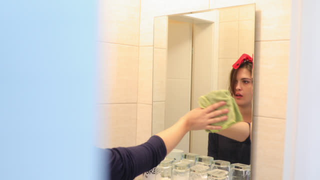 young woman doing house work with headband on. bathroom cleaning is really boring - headband stock videos & royalty-free footage
