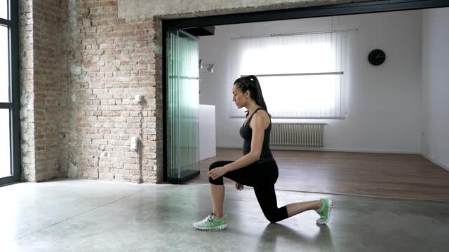 vidéos et rushes de jeune femme faisant des mouvements brusques de saut à la maison - aérobic