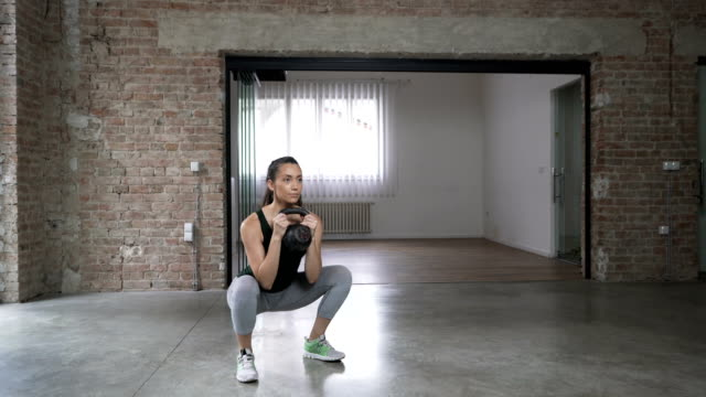 young woman doing kettlebell goblet squats - crouching stock videos & royalty-free footage