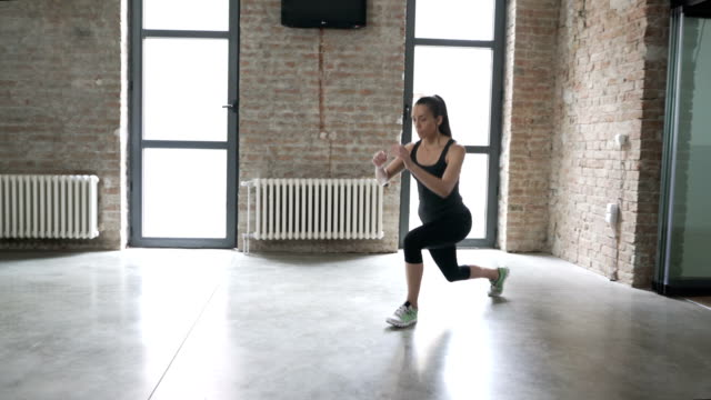 young woman doing lunge variations at home - stretching stock videos & royalty-free footage