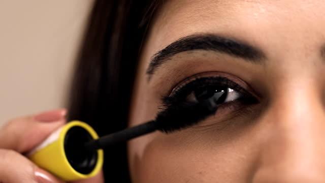 Young woman doing make-up, Delhi, India