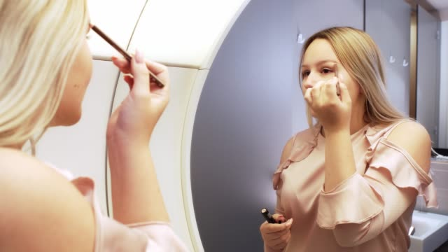 Young woman doing makeup in front of mirror
