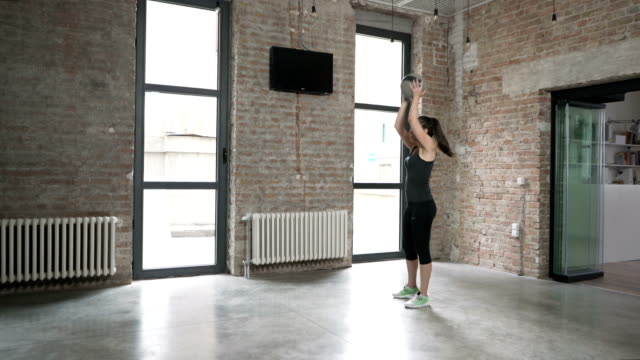 Young Woman Doing Medicine Ball Overhead Lunges
