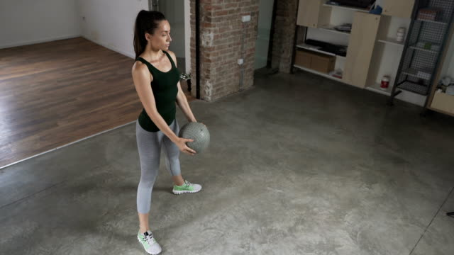 Young Woman Doing Medicine Ball Squats