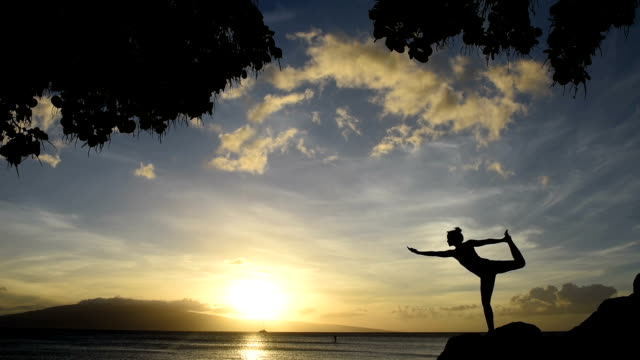 Young woman doing oceanside yoga at sunset