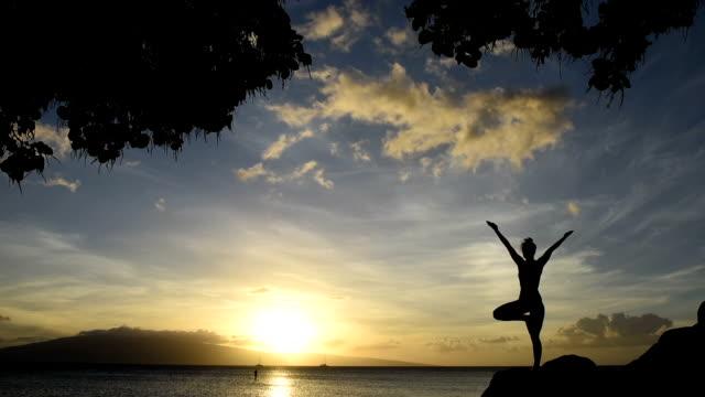 vídeos y material grabado en eventos de stock de joven mujer haciendo yoga de oceanside al anochecer - vriksha asana