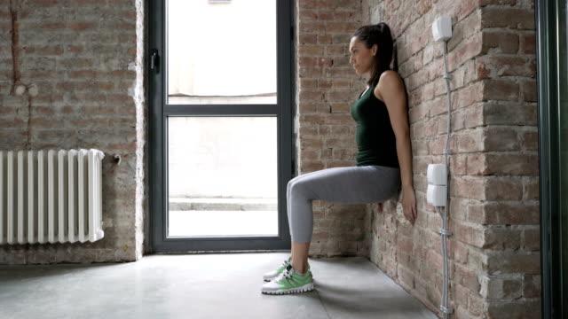 vídeos y material grabado en eventos de stock de mujer joven haciendo una pared piernas sentadillas - pilates
