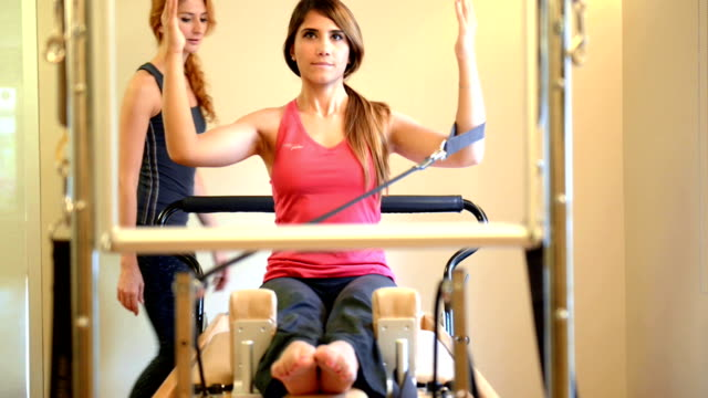 dolly: young woman doing pilates exercise with instructor - pilates stock videos and b-roll footage