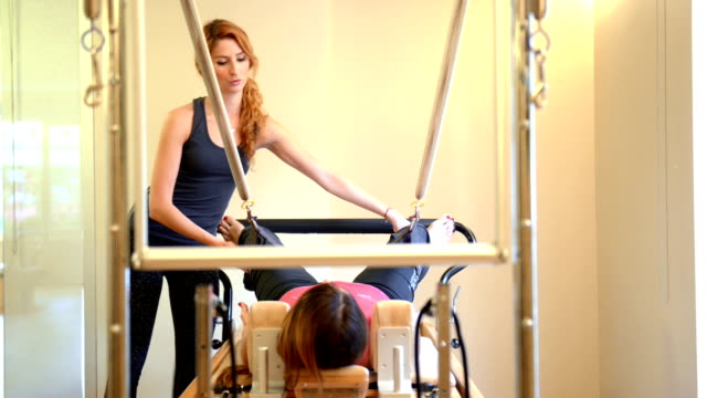DOLLY: Young woman doing pilates exercise with instructor