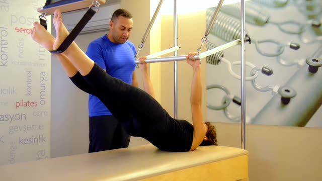 vídeos y material grabado en eventos de stock de dolly: mujer joven haciendo ejercicios de pilates con instructor - pilates