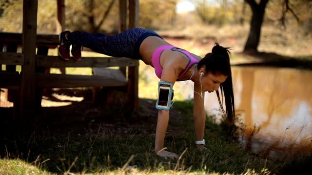 vídeos y material grabado en eventos de stock de mujer joven haciendo ejercicio de tablón en la naturaleza - entrenamiento sin material