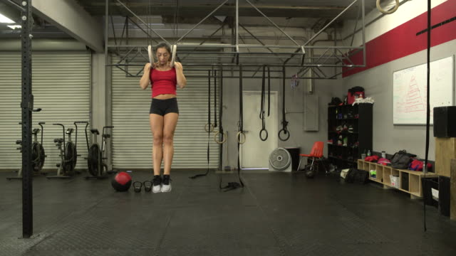 WS Young woman doing pull ups on rings in a gym