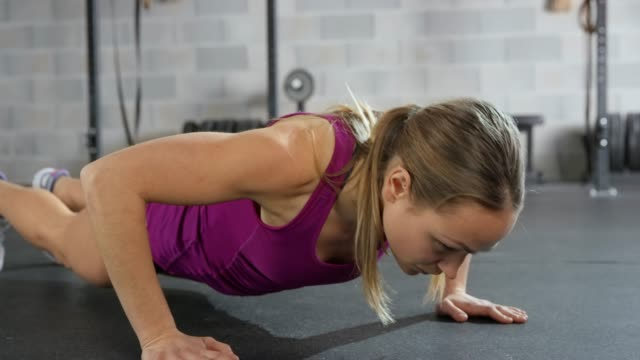 young woman doing push ups in the fitness center - one young woman only stock videos & royalty-free footage