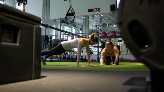 vídeos y material grabado en eventos de stock de young woman doing push-ups in a gym - entrenamiento sin material