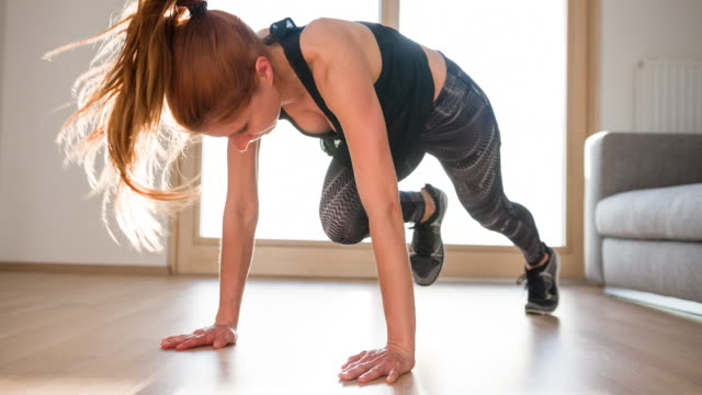 Young woman doing running plank workout