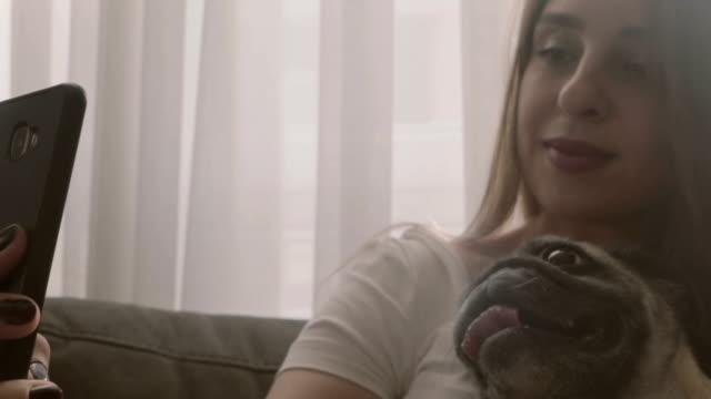 家で彼女の犬と selfies をする若い女性 - photographing点の映像素材/bロール