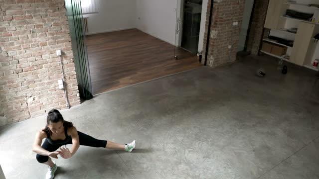 vídeos y material grabado en eventos de stock de mujer joven haciendo estocadas laterales en casa - aeróbic